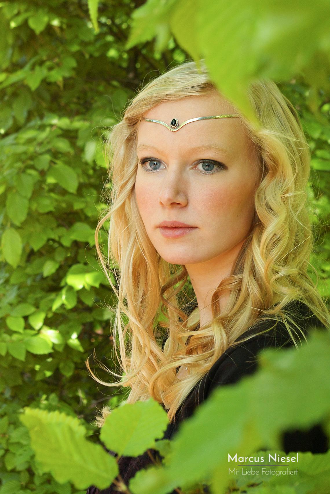 Eine junge Frau tritt zwischen grünen Hecken hervor und schaut in die Ferne. Sie trägt ein Diadem und hat blondes Haar.