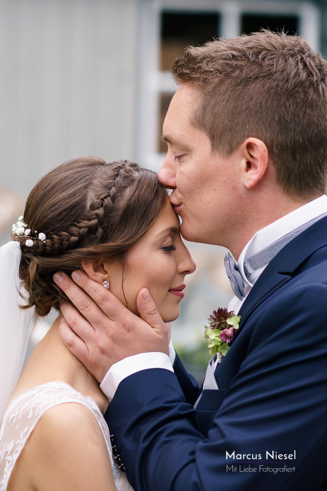 Inniger Kuss auf die Stirn. Hochzeitsfotograf Marcus Niesel fotografiert in Ettenheim.