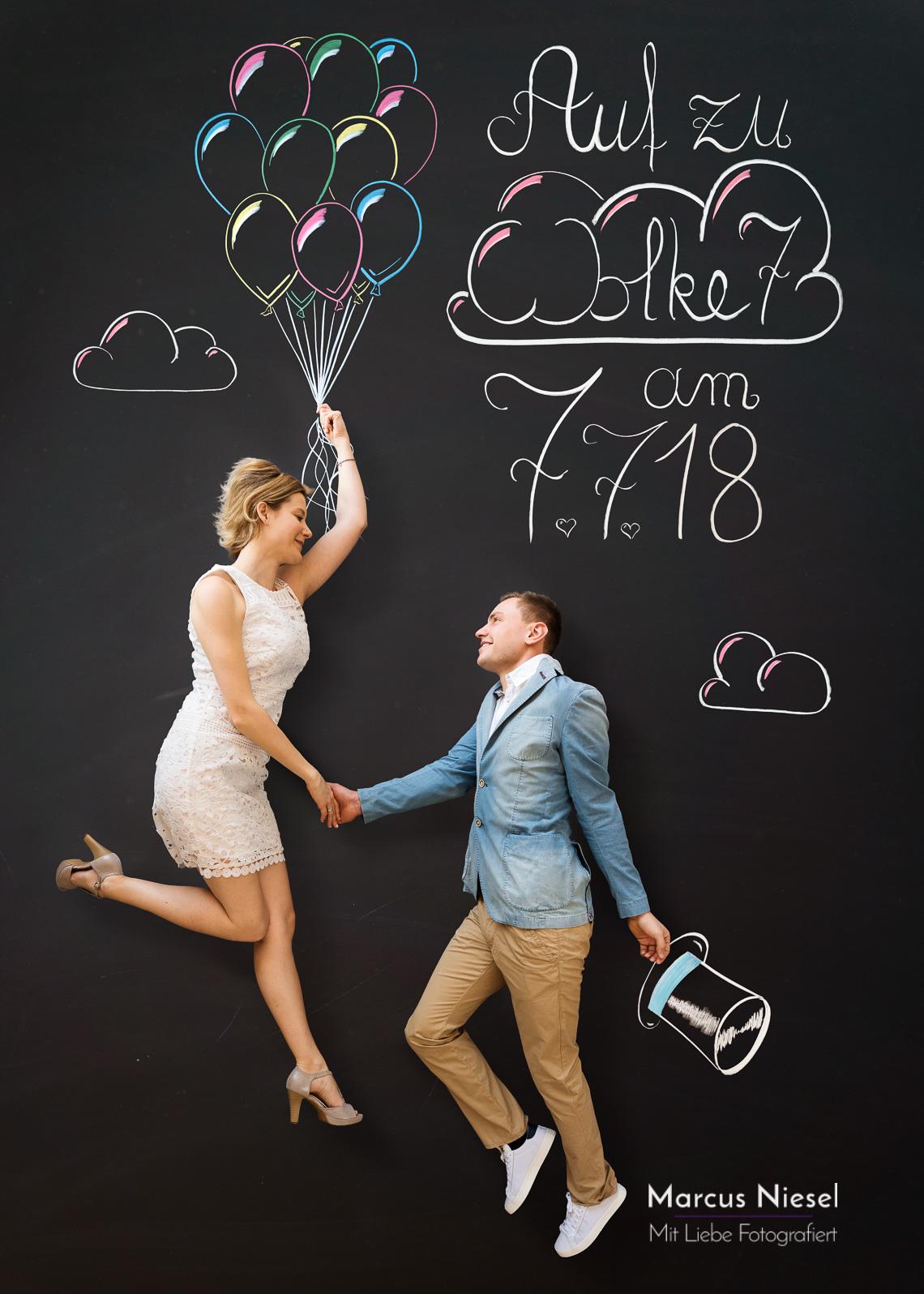 Ein Paar schaut sich liebevoll in die Augen und fliegt imaginar an Luftballons hängend hinauf zu Wolke 7.