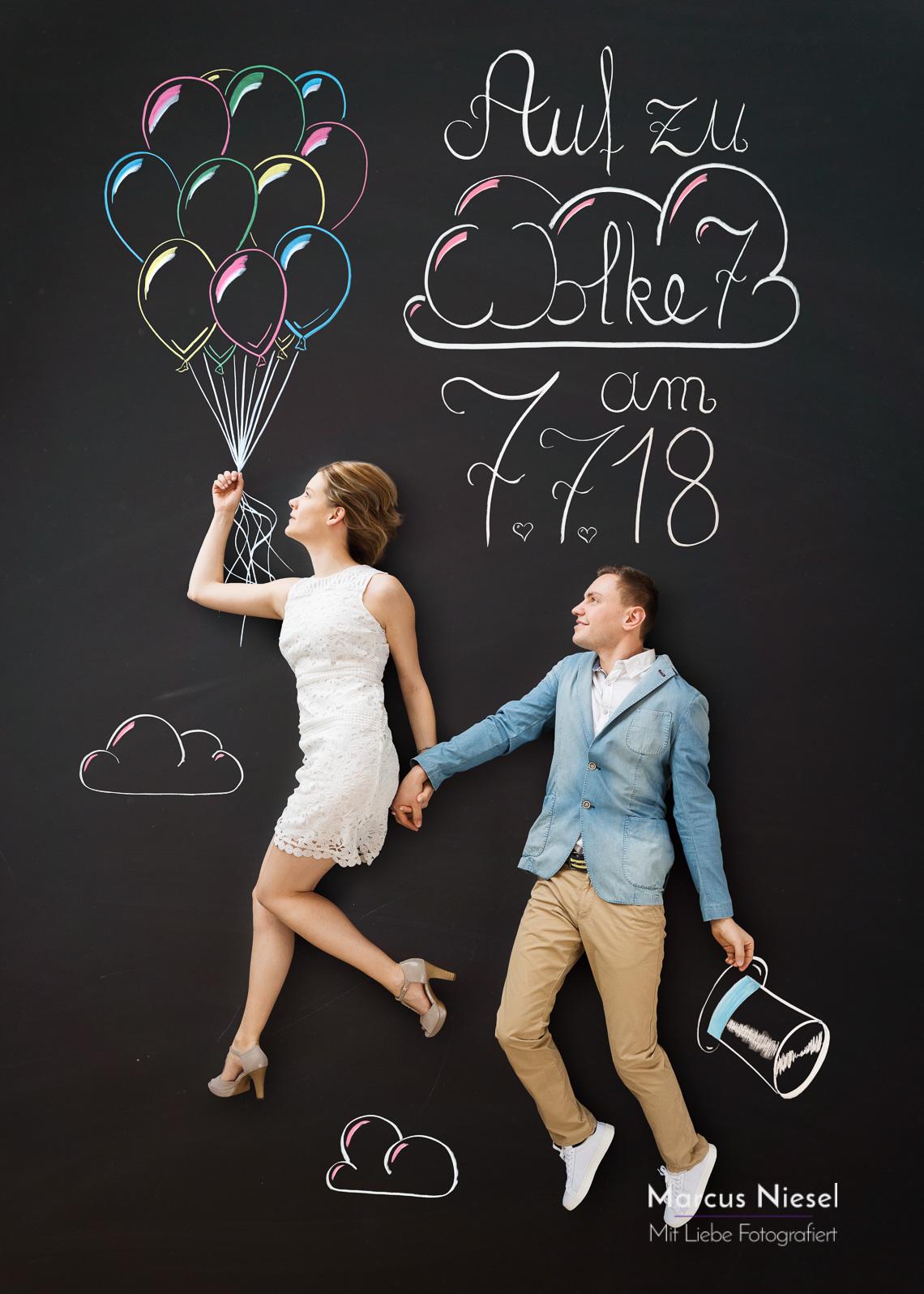 Ein Paar schwebt Hand in Hand an einem großen Bündel Luftballons hängen der Wolke 7 entgegen. Ihrem Hochzeitstag am 7.7.18. Fotograf und Kreidekünstler - Marcus Niesel