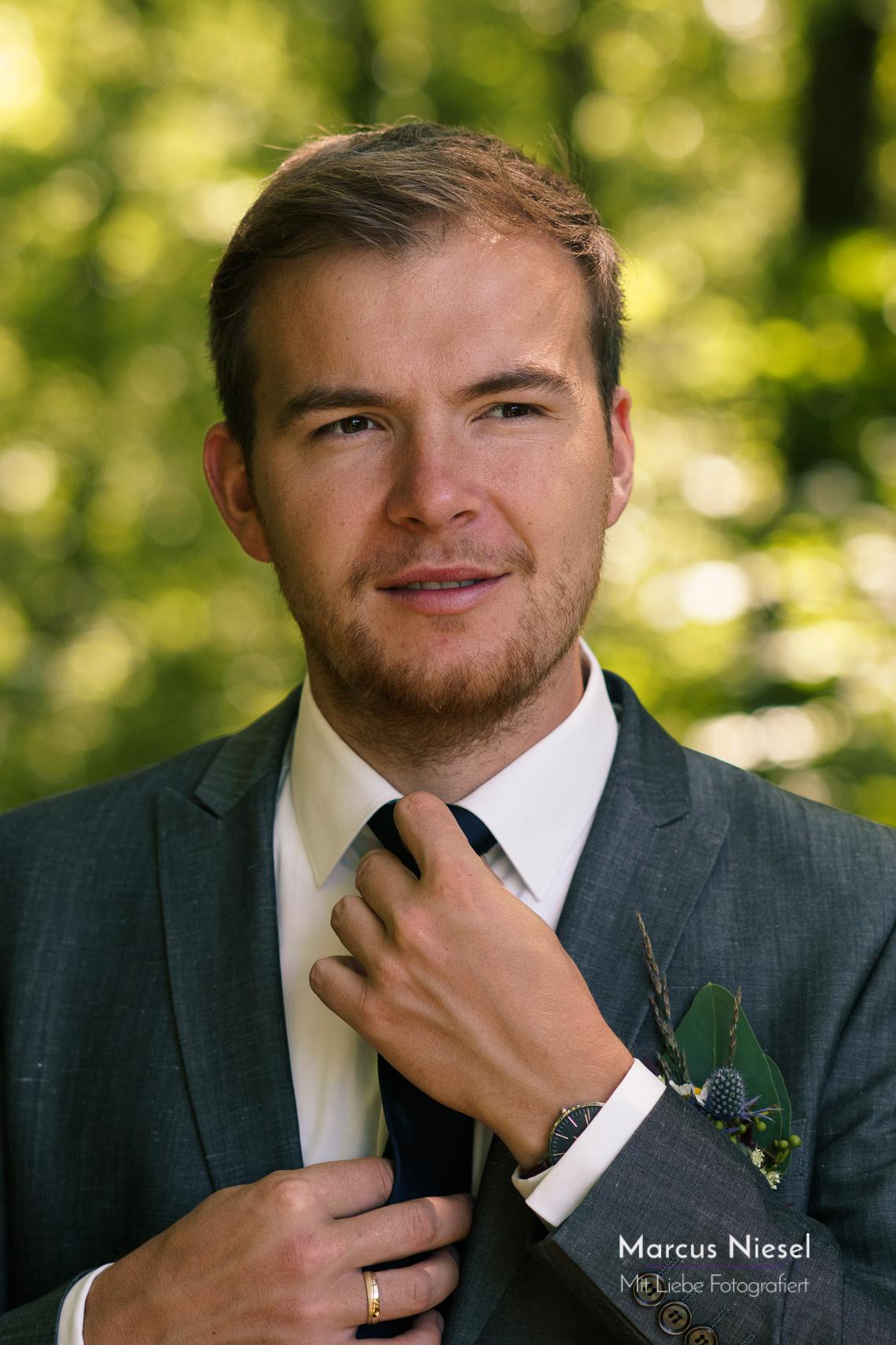 Der Bräutigam rückt seine Krawatte für das Foto zurecht.