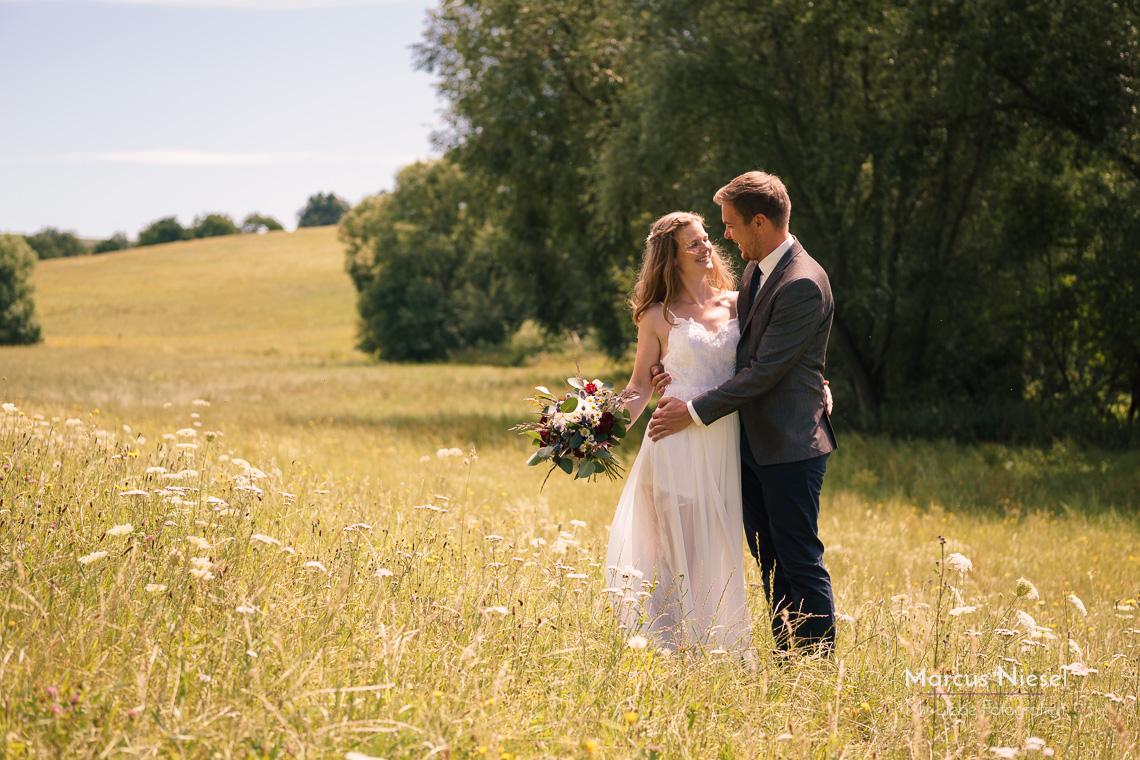 Das Brautpaar auf der grünen Sommerwiese sieht sich das erste Mal. Die Sonne scheint und die Farben sind schon sommerlich gelb.